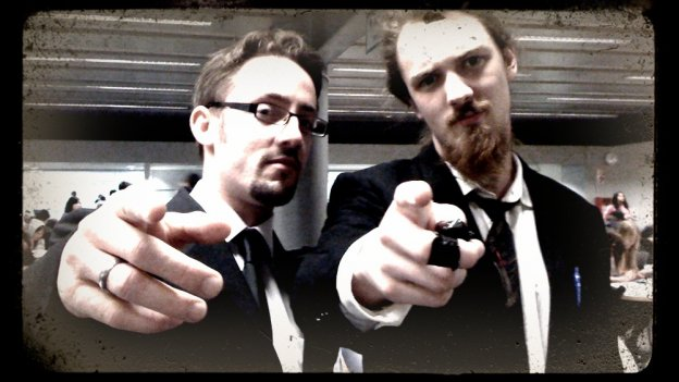 two young people in suits pointing