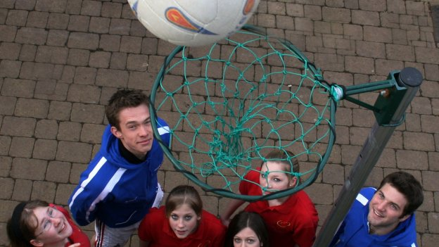 youngsters looking up at netball net