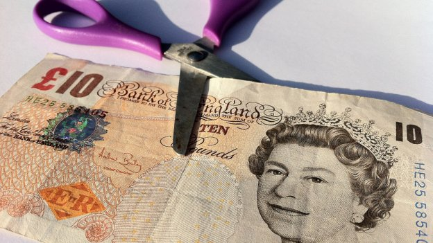 £10 note and scissors
