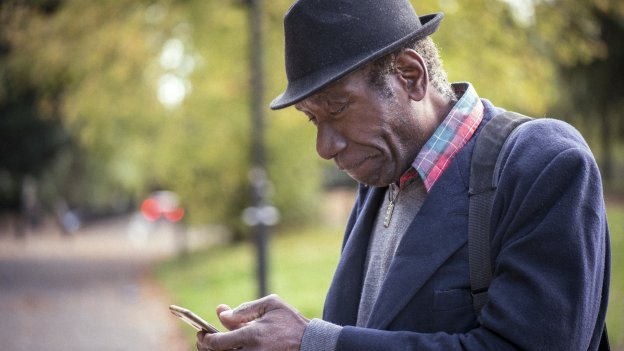 Older gentleman looking at smartphone in a park