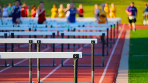 photo of people in a race jumping hurdles