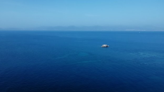 Picture of blue uninterrupted ocean meeting the sky, which is a lighter blue than the dark blue of the sea