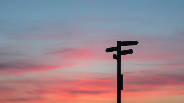 Orange sunset with the silhouette of a roadsign pointing in lots of directions in front of it