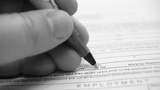 Person filling out application with a pen