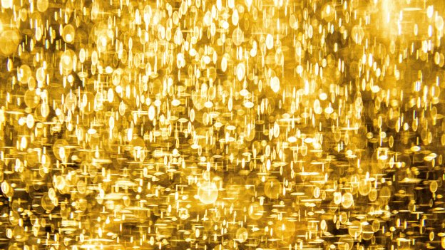 Gold glitter shining against a dark background