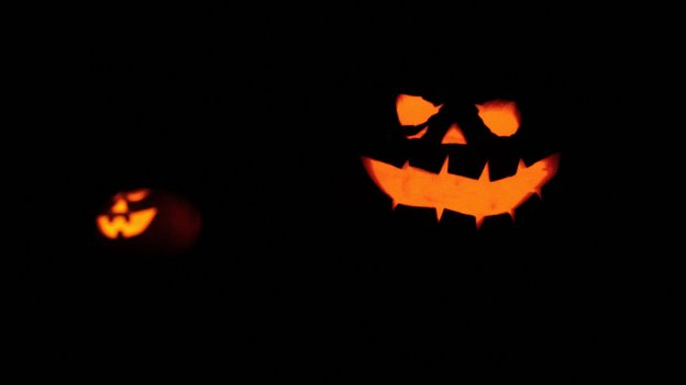 Two halloween pumpkins with faces illuminated in the dark