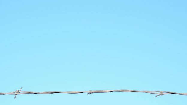 Single line of barbed wire against clear blue sky background