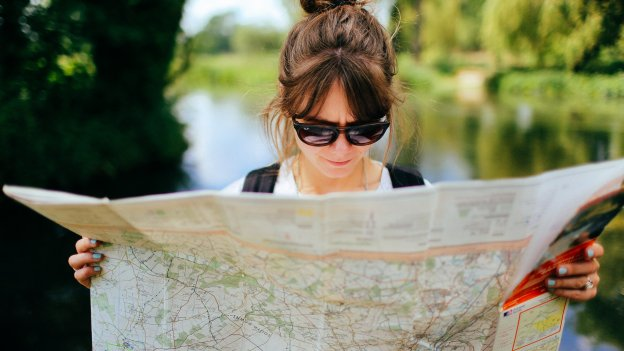 White woman wearing sunglasses looks at a map on a sunny day
