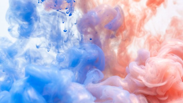 image of watercolour paint splashed into water, blue on left side red on right side
