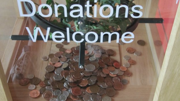 Image of charity donation box with some money in it and a 'donations welcome' sign