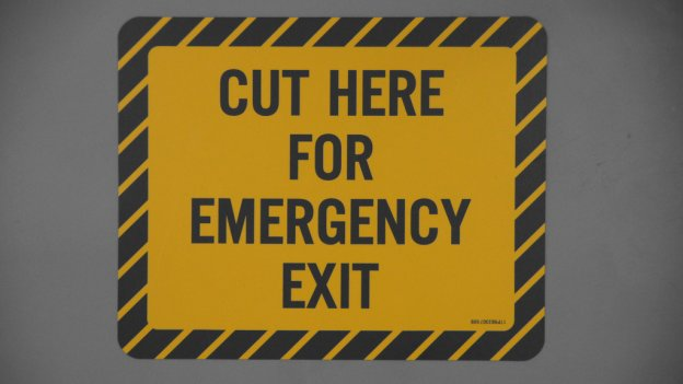 Warning sign which reads 'Cut here for emergency exit'