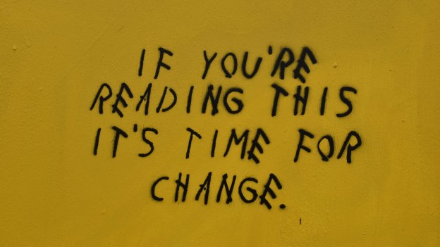 Black stencil graffiti text reading 'If you're reading this it's time for change' against a yellow background