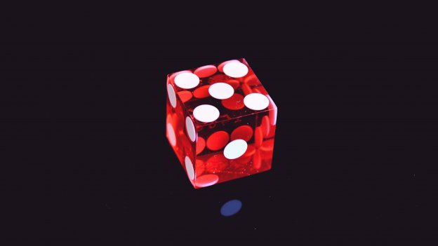 Red die showing number 4 against black background